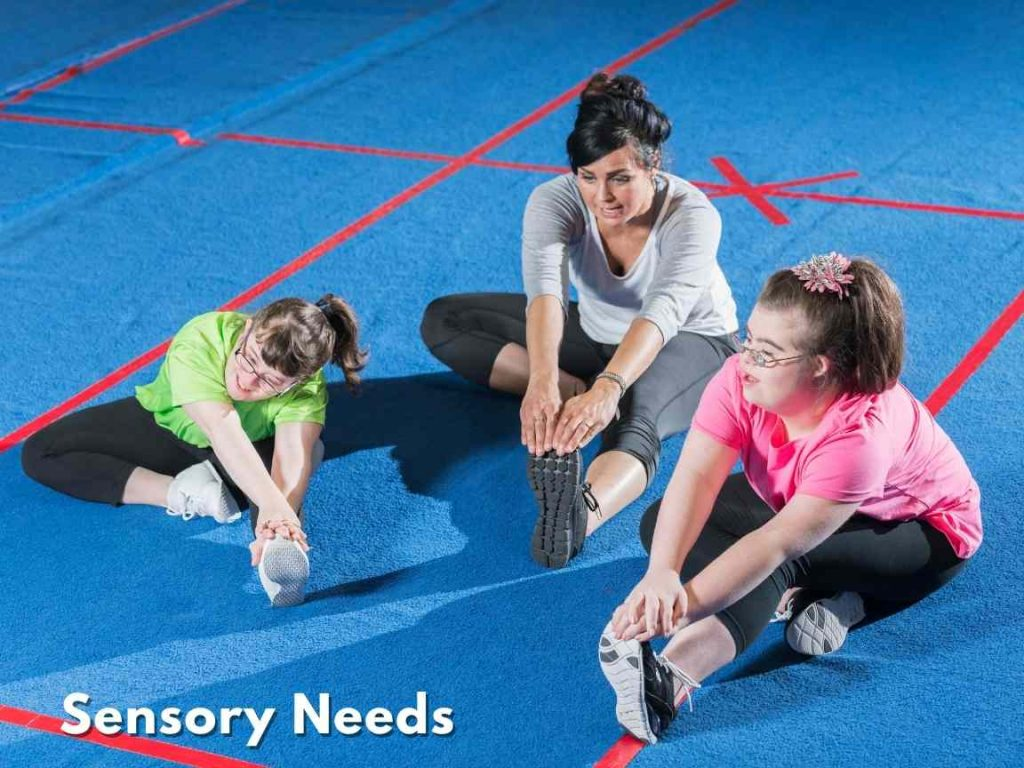 special needs children stretching out with their gym teacher on the floor